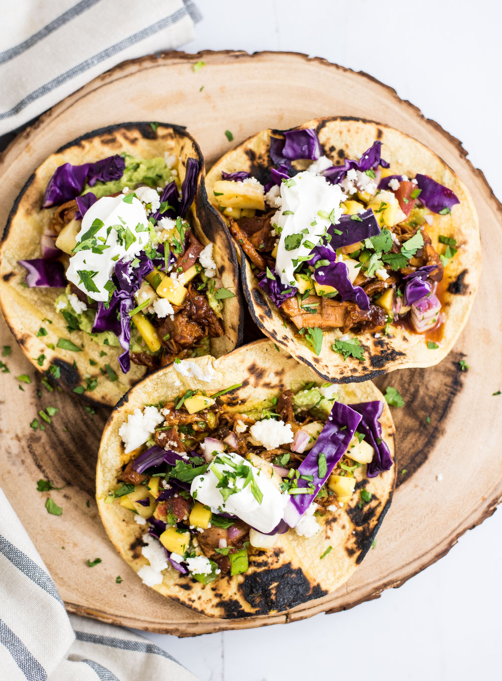 Slow cooker barbecue chicken tacos with mango and pineapple salsa are the perfect way to spruce up your Taco Tuesday. They are simple and super flavorful!