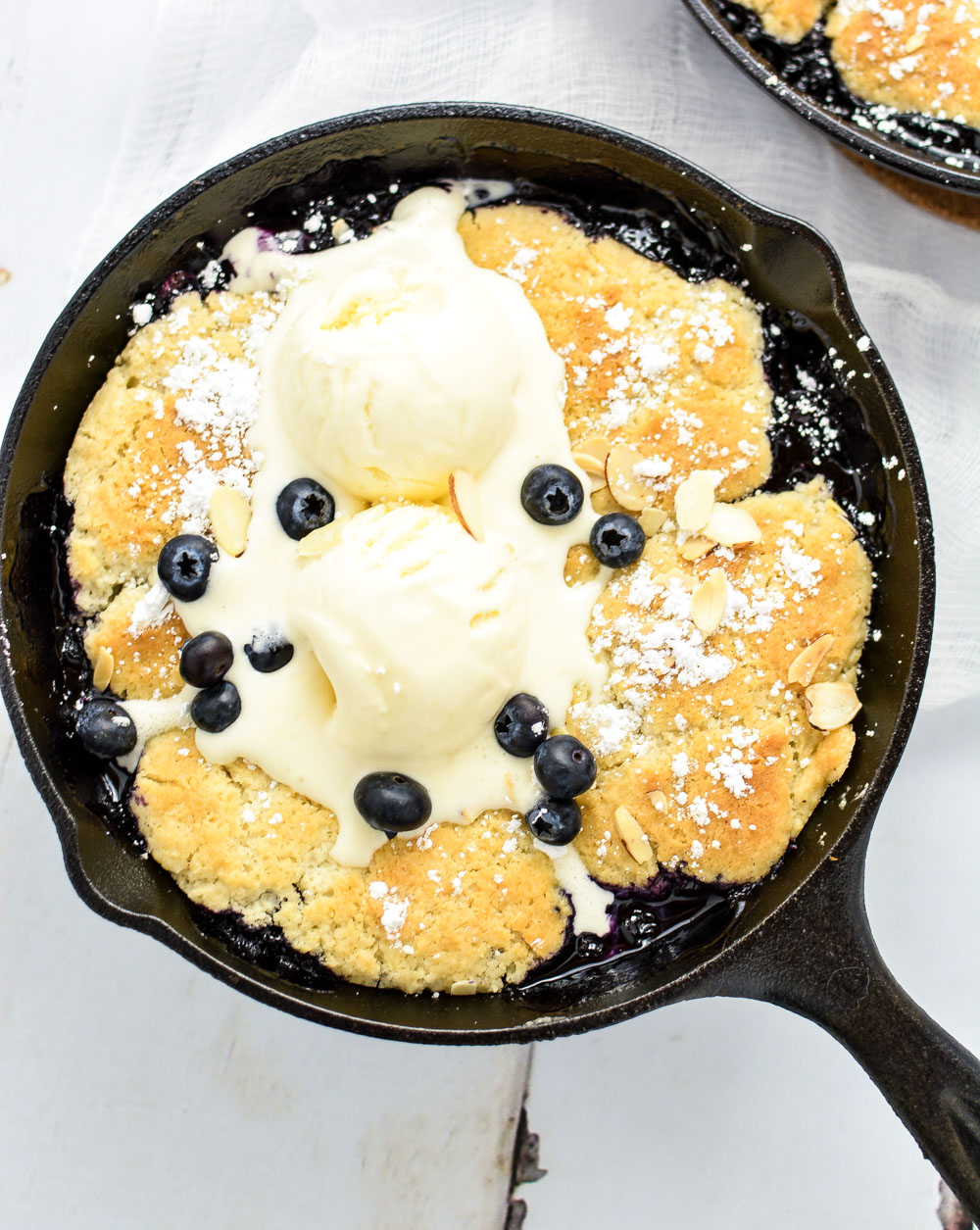 Sweet Bourbon Blueberry Cobbler is a must-have dessert recipe for the summertime that has a hint of bourbon sweetness and a burst of blueberry tartness!