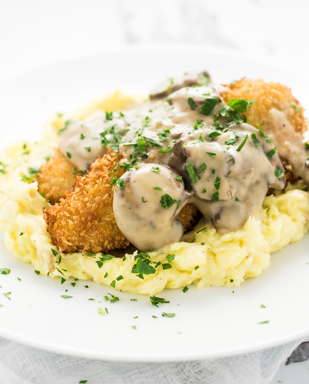 Pork Schnitzel with Mushroom Stout Gravy is a twist on a classic Austrian dish that is loaded with flavor and coated with crispiness!